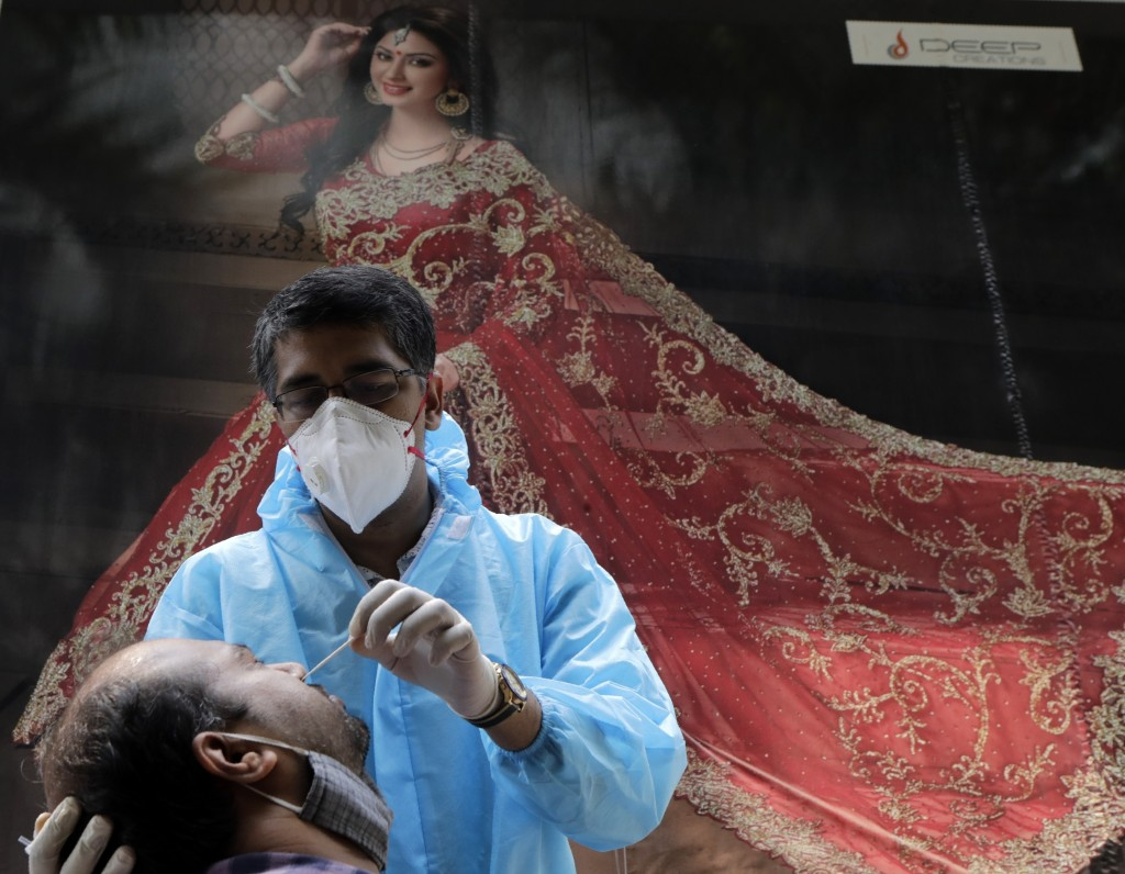 A health worker takes swab sample of a woman to test for COVID-19 outside a garment shop in Mumbai, India, Tuesday, Oct. 13, 2020. The country of near...