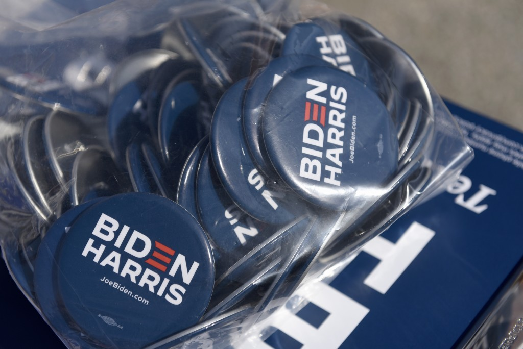 Biden/Harris pins are displayed by the Joe Biden campaign are seen on a table at an early voting satellite location at the Anne B. Day elementary scho...