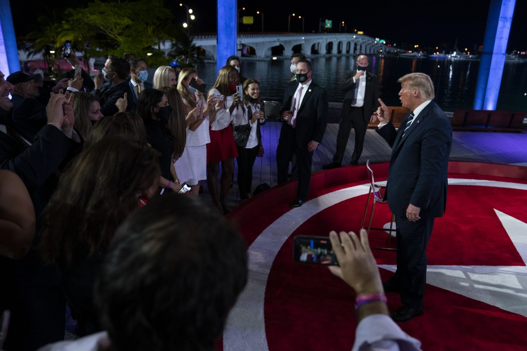 President Donald Trump talks with voters after an NBC News Town Hall, at Perez Art Museum Miami, Thursday, Oct. 15, 2020, in Miami. (AP Photo/Evan Vuc...