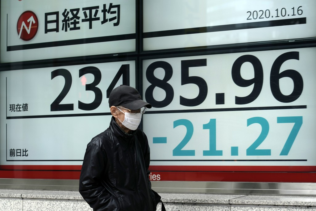 A man walks past an electronic stock board showing Japan's Nikkei 225 index at a securities firm in Tokyo Friday, Oct. 16, 2020. Asian shares were mix...