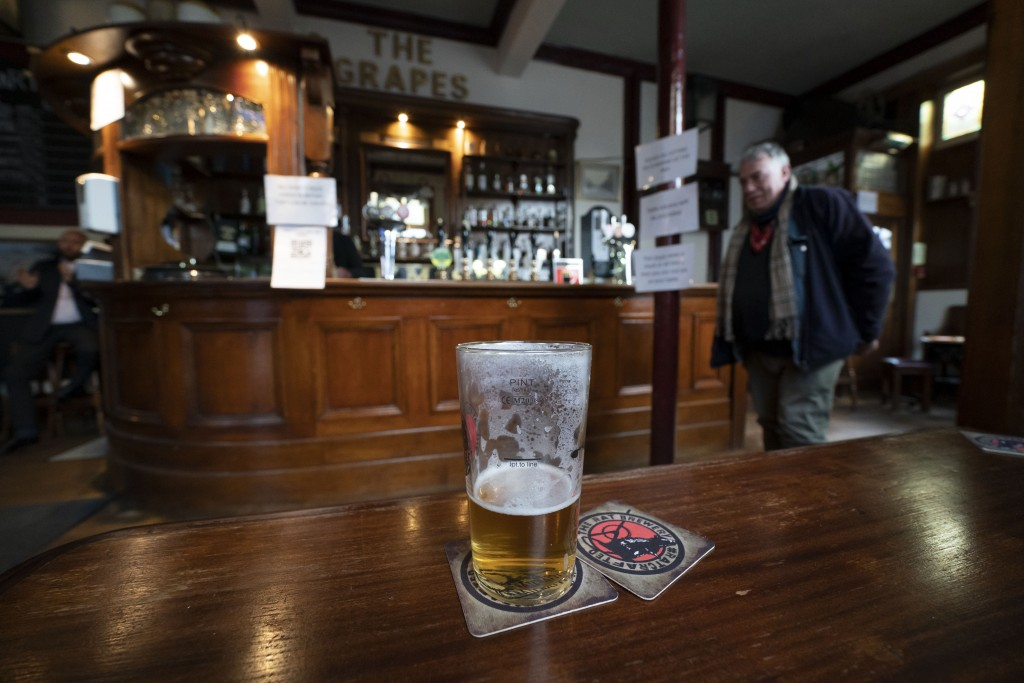 A half-full beer glass remains on a table at the Dispensary pub in Liverpool, England, Monday Oct 12, 2020. As the first area in England slapped with ...