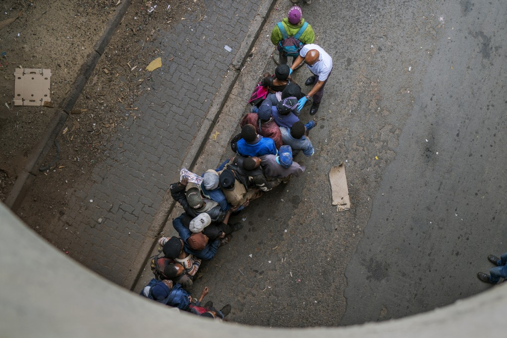 FILE — In this Monday, April 13, 2020 file photo, homeless people queue for food parcels from private donors in downtown Johannesburg. South African P...