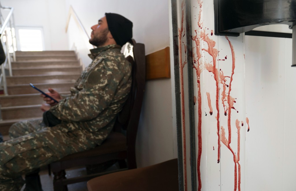 An Armenian serviceman rests near a bloody door in a hospital damaged by shelling from Azerbaijan's artillery in the town of Martakert, the separatist...