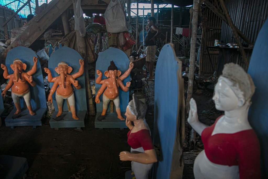 An Indian artisan speaks on a phone as he works on idols of Hindu gods and goddesses ahead of Durga Puja festival in Gauhati, India, Friday, Oct. 16, ...