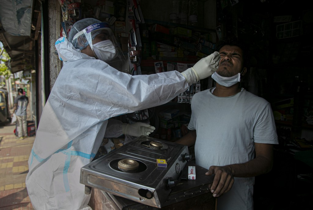 A health worker takes a nasal swab sample of a shopkeeper during random testing for COVID-19 in a market in Gauhati, India, Friday, Oct. 16, 2020. Ind...
