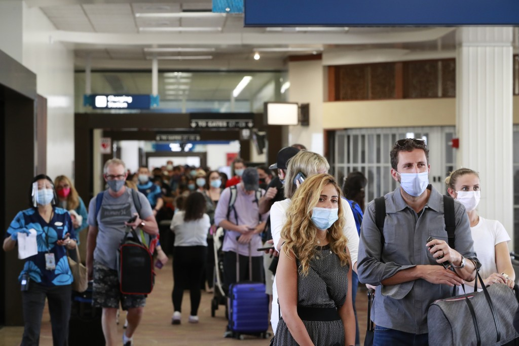 Visitors line a corridor in the Daniel K. Inouye International Airport as they enter the state, Thursday, Oct. 15, 2020, in Honolulu. A new pre-travel...