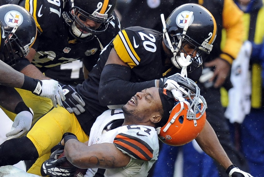 FILE  - In this Dec. 29, 2013, file photo, Cleveland Browns running back Edwin Baker (27) loses his helmet as he is tackled by Pittsburgh Steelers str...