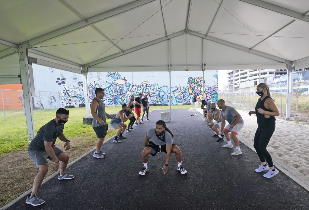Trainer Legend Tarvers, center, leads a group during a workout at Legacy Fit, Monday, Aug. 31, 2020, in Miami. As the vast majority of in-person fitne...