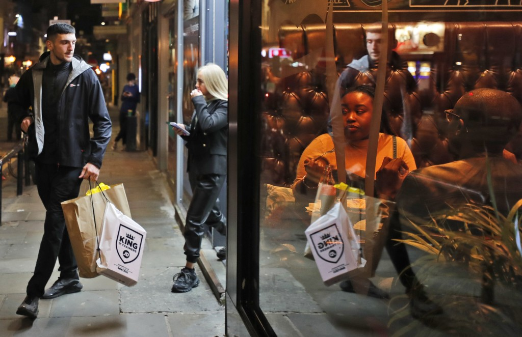 Shoppers walk past people eating in a restaurant in Liverpool, England, Wednesday, Oct. 14, 2020. As the first area in England slapped with strict new...