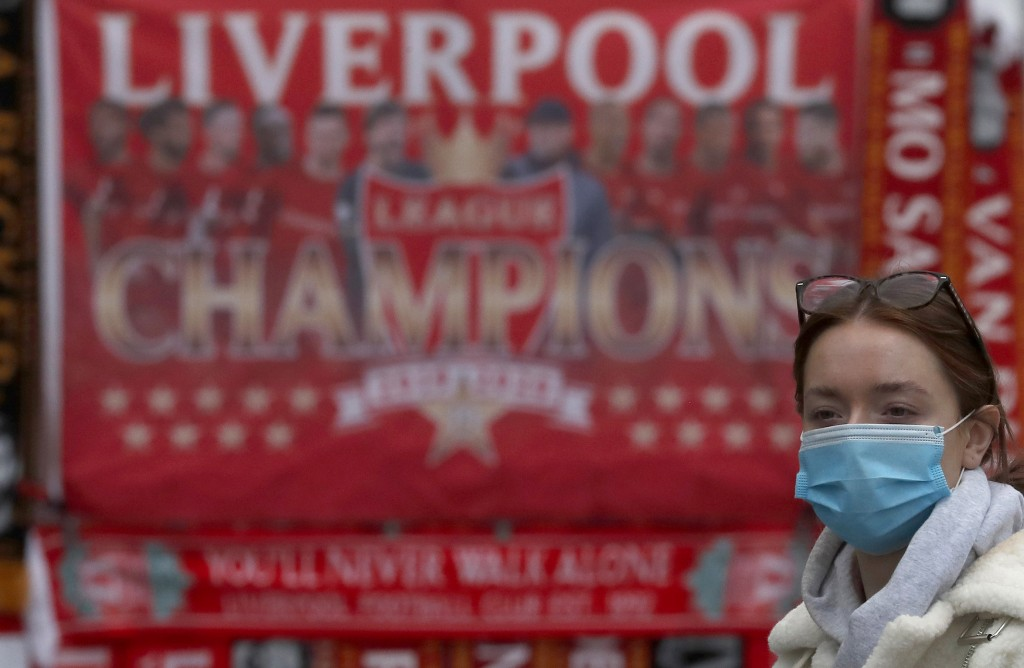 A woman wearing a face-covering walks past Liverpool soccer club merchandise on sale in Liverpool, England, Wednesday, Oct. 14, 2020. Scarred by aband...
