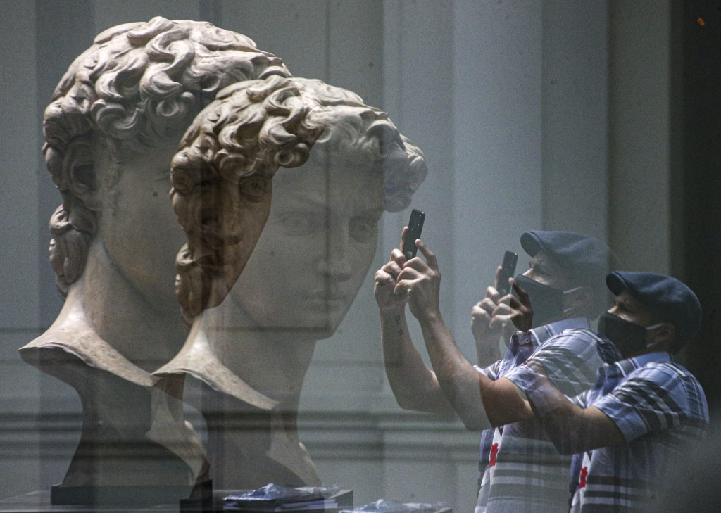 "A visitor is reflected in glass as he takes a picture of a replica of the head of Michelangelo's sculpture ""David"" at the National Museum of Fine Arts..."
