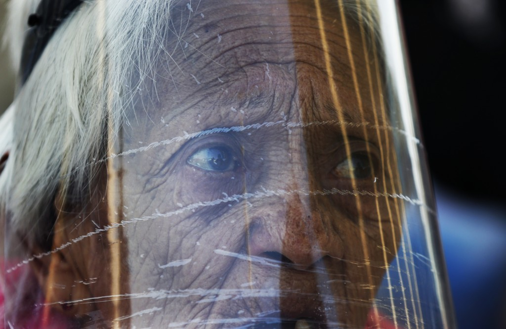 An elderly woman wearing a face shield to curb the spread of the new coronavirus waits her turn in line to be given coupons provided by the municipali...
