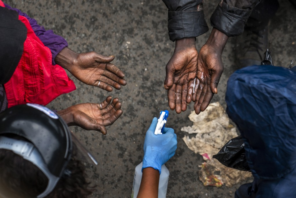 FILE — In this Monday, April 13, 2020 file photo, homeless people have their hands sanitised while they wait to receive food baskets from private dono...