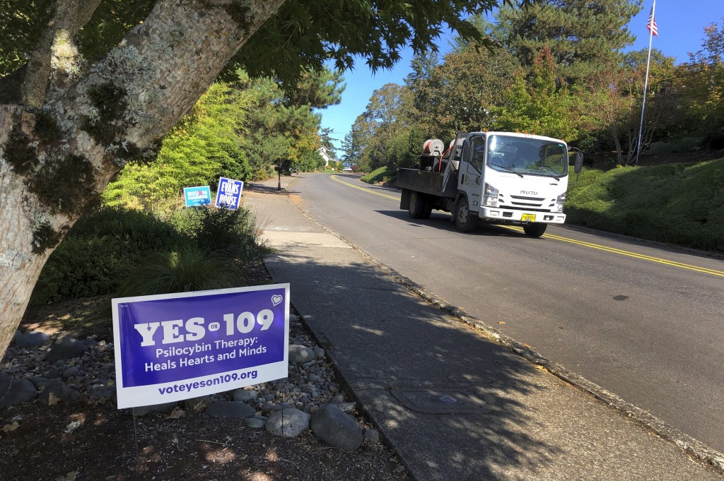 A truck drives past a sign supporting a ballot measure that would legalize controlled, therapeutic use of psilocybin mushrooms, Friday, Oct. 9, 2020 i...