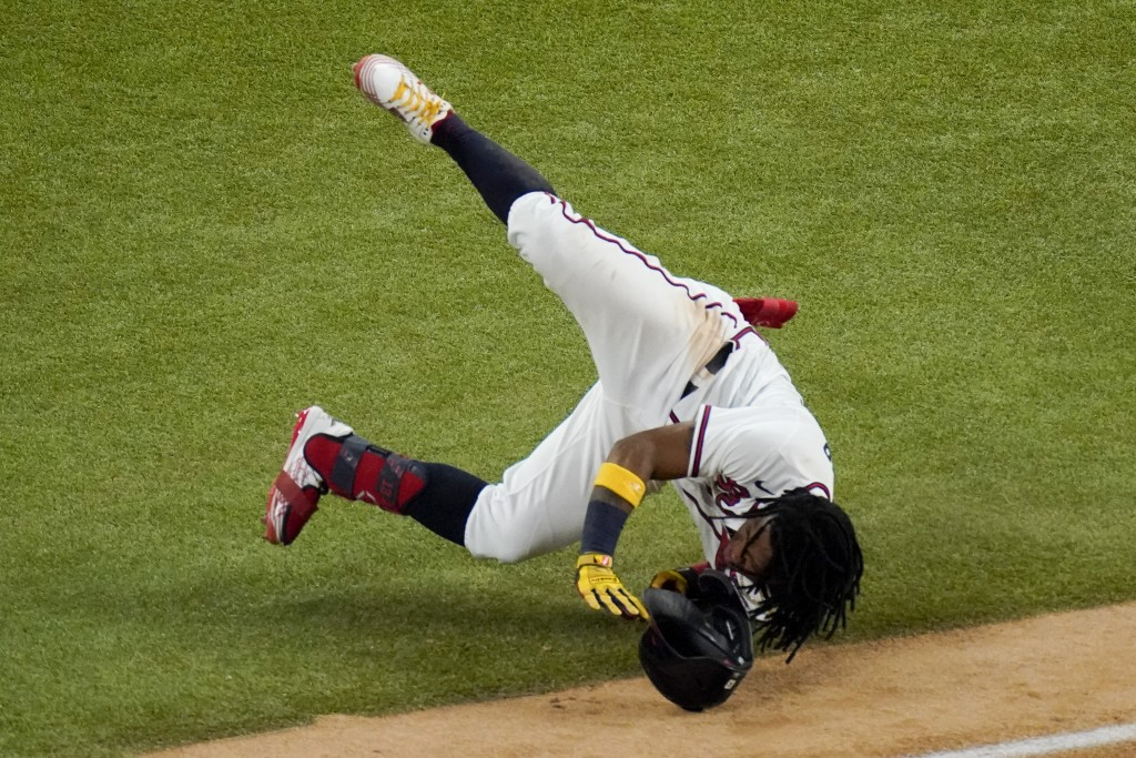 Atlanta Braves' Ronald Acuna Jr. falls at first base during the sixth inning in Game 4 of a baseball National League Championship Series against the L...