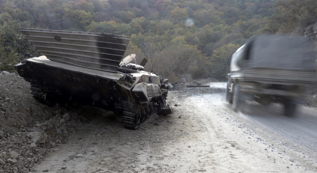 A truck drives past a destroyed Armenian APC on the road from Stepanakert to Martekert during a military conflict in the separatist region of Nagorno-...