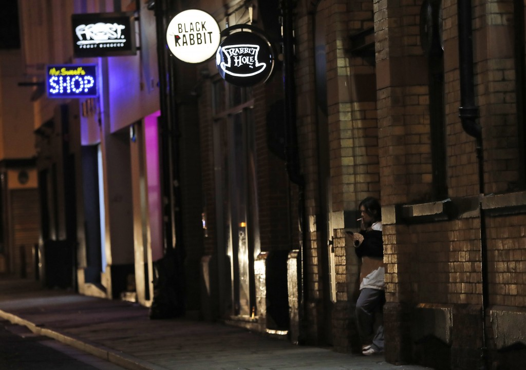 A person smokes a cigarette on a street full of closed bars and pubs in Liverpool, England, Wednesday, Oct. 14, 2020. As the first area in England sla...