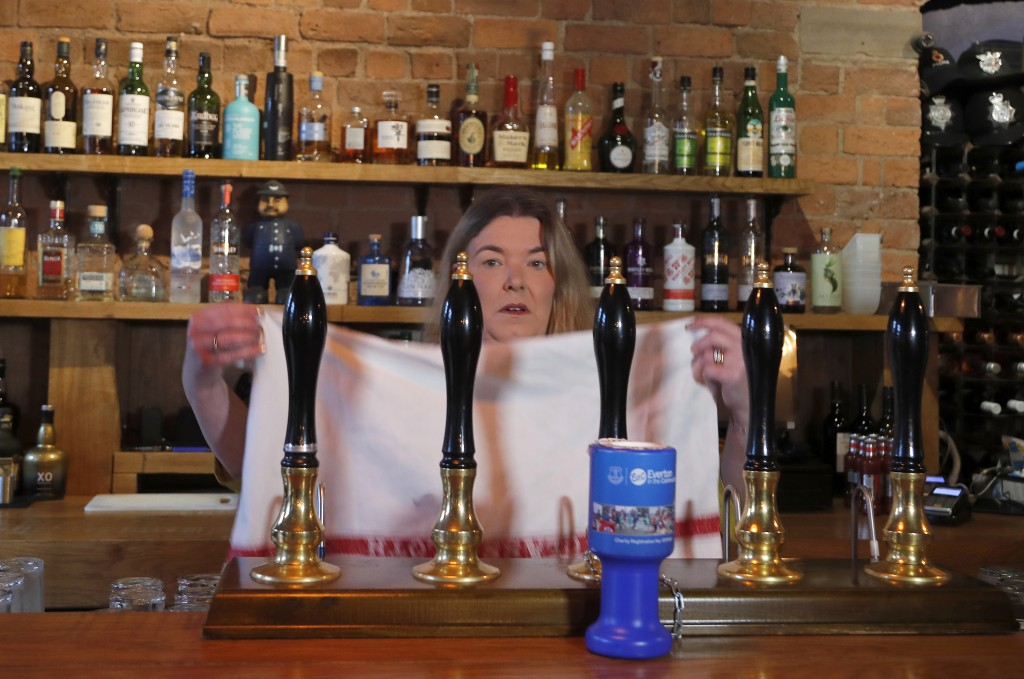 Fiona Hornsby, the owner of the Bridewell pub puts a towel over the beer taps in Liverpool, England, Wednesday, Oct. 14, 2020. As the first area in En...