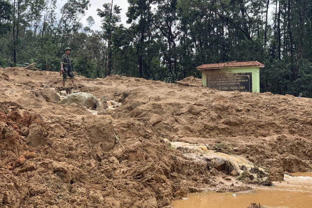 An army officer stands at the site of a landslide at a forest ranger outpost in Thua Thien-Hue province, Vietnam, Thursday, Oct. 15, 2020. Rescuers re...