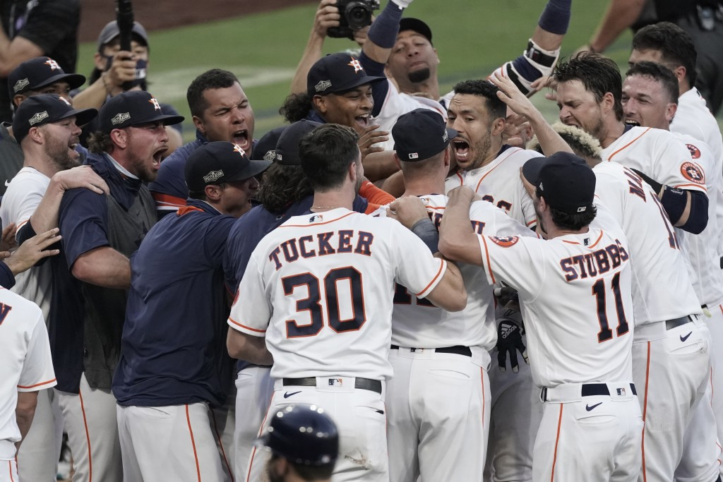 CORRECTS TO THURSDAY, OCT. 15, 2020, NOT TUESDAY, DEC. 15, 2020 - Houston Astros Carlos Correa celebrates with teammates after his walk off home run d...