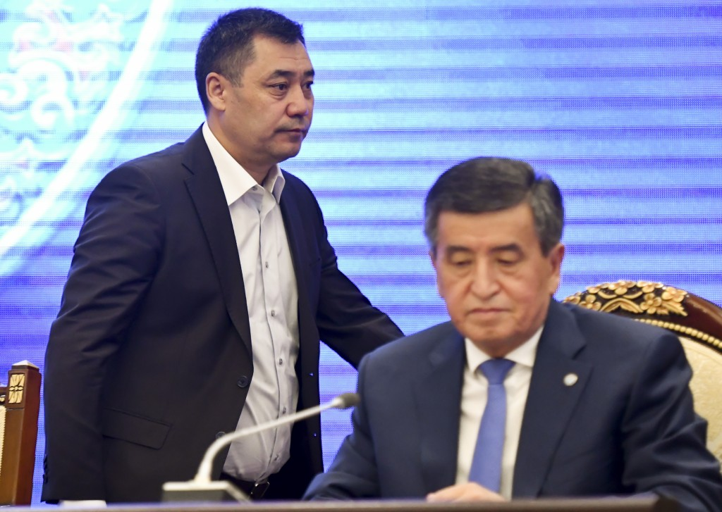 Kyrgyzstan's Prime Minister Sadyr Zhaparov, left, walks behind Kyrgyzstan's President Sooronbai Jeenbekov during an official transfer of power ceremon...