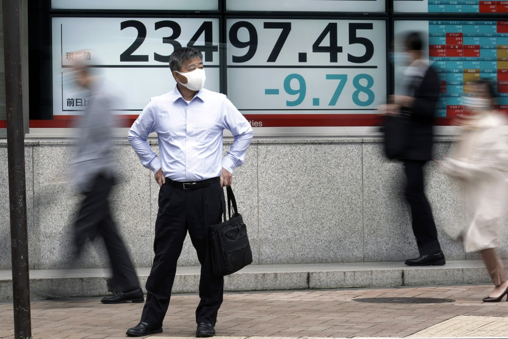A man stands near an electronic stock board showing Japan's Nikkei 225 index at a securities firm in Tokyo Friday, Oct. 16, 2020. Asian shares were mi...