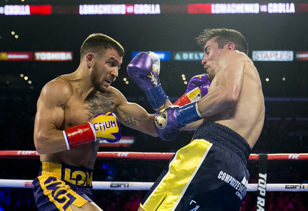 FILE - In this April 12, 2019, file photo, Vasiliy Lomachenko, left, from Ukraine, hits Anthony Crolla, from Britain, during a WBA and WBO lightweight...