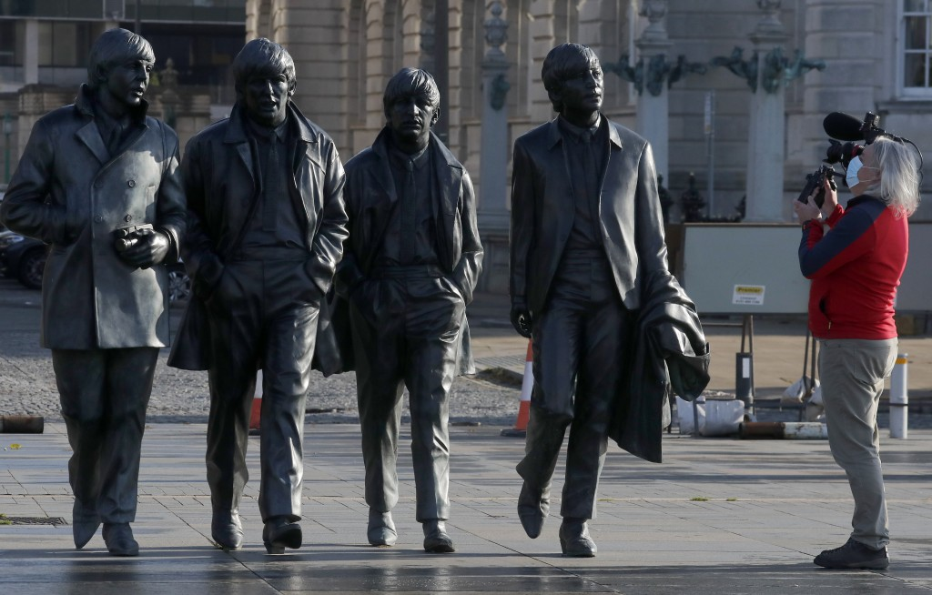 A video journalist films the Beatles statue in Liverpool, England, Wednesday, Oct. 14, 2020. Liverpool, the English port city that gave the world the ...