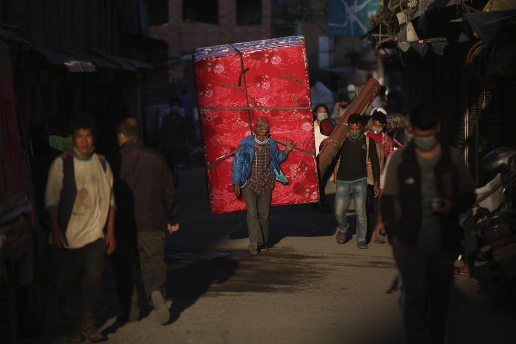 A Nepalese man wearing a mask as a precautionary measure against the coronavirus walks in a market area in Kathmandu, Nepal, Friday, Oct. 9, 2020. (AP...