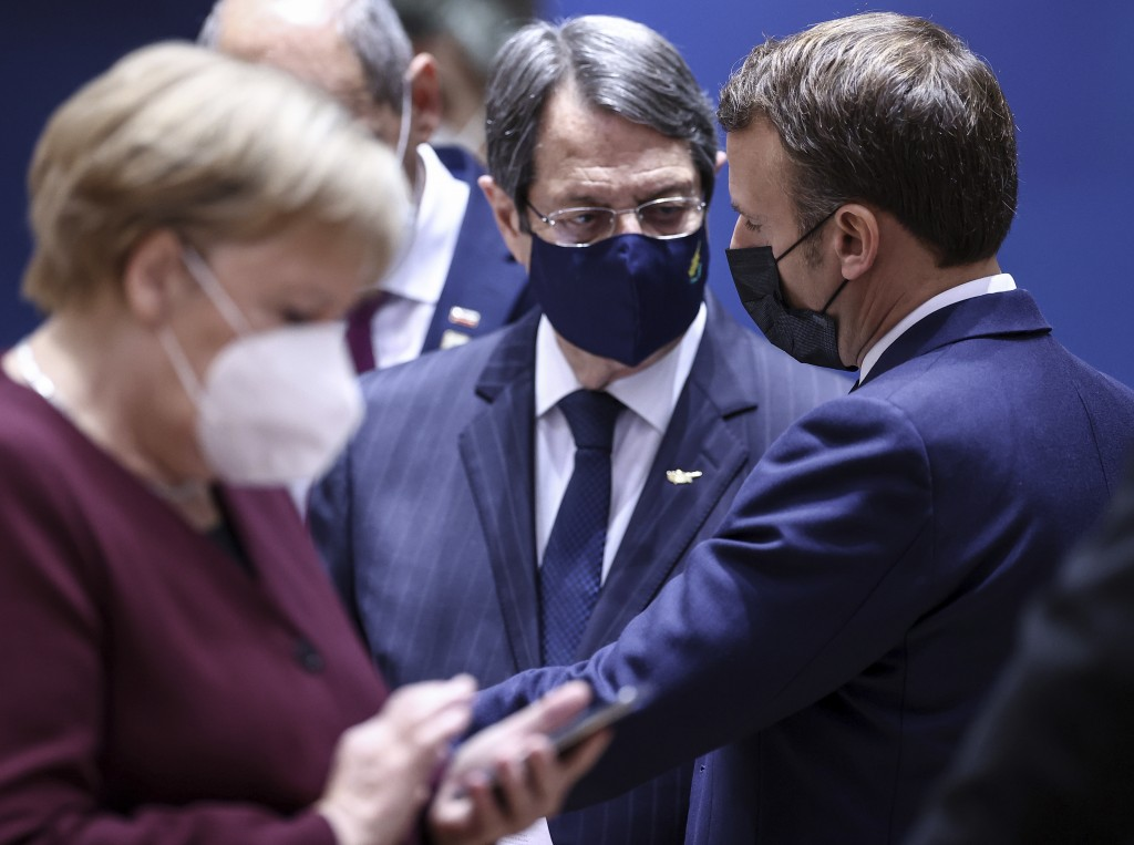 Cypriot President Nicos Anastasiades, center, speaks with French President Emmanuel Macron, right, during a round table meeting at an EU summit in Bru...