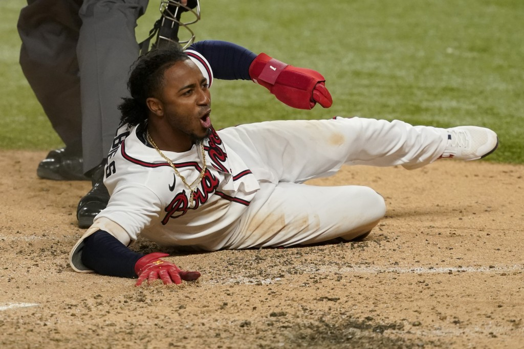 Atlanta Braves' Ozzie Albies scores on a double by Dansby Swanson during the sixth inning in Game 4 of a baseball National League Championship Series ...