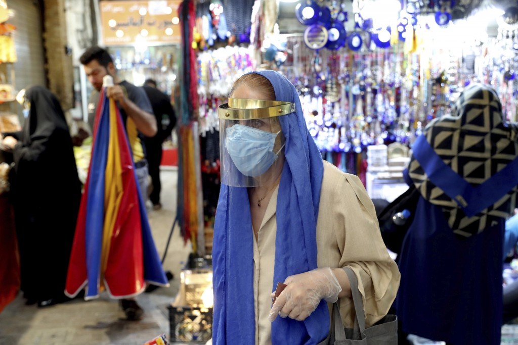 A woman wearing a protective face mask and gloves to help prevent the spread of the coronavirus walks through the Tajrish traditional bazaar in northe...