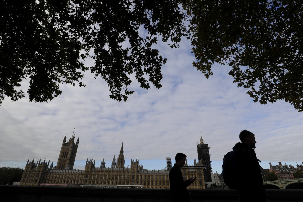 People walk opposite Britain's Parliament in London, Friday, Oct. 16, 2020. Britain's foreign minister says there are only narrow differences remainin...