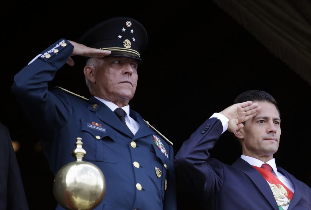 FILE - In this Sept. 16, 2016 file photo, Defense Secretary Gen. Salvador Cienfuegos, left, and Mexico's President Enrique Pena Nieto, salute during t...