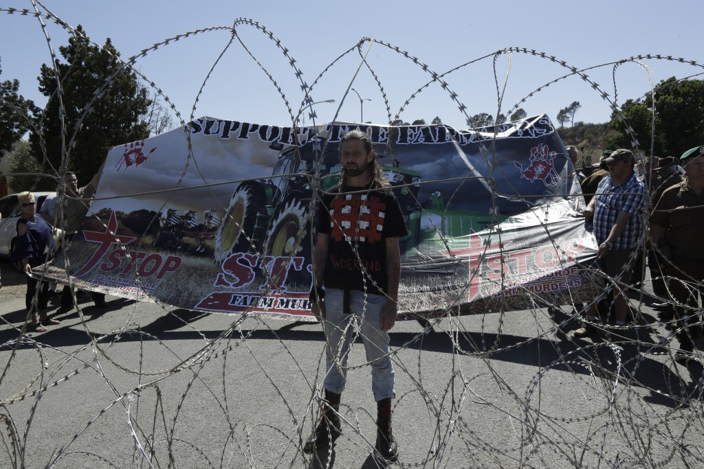 A protester against the recent farm murder, stands behind a a razorwire barricade near the magistrates court in Senekal, South Africa, Friday, Oct. 16...