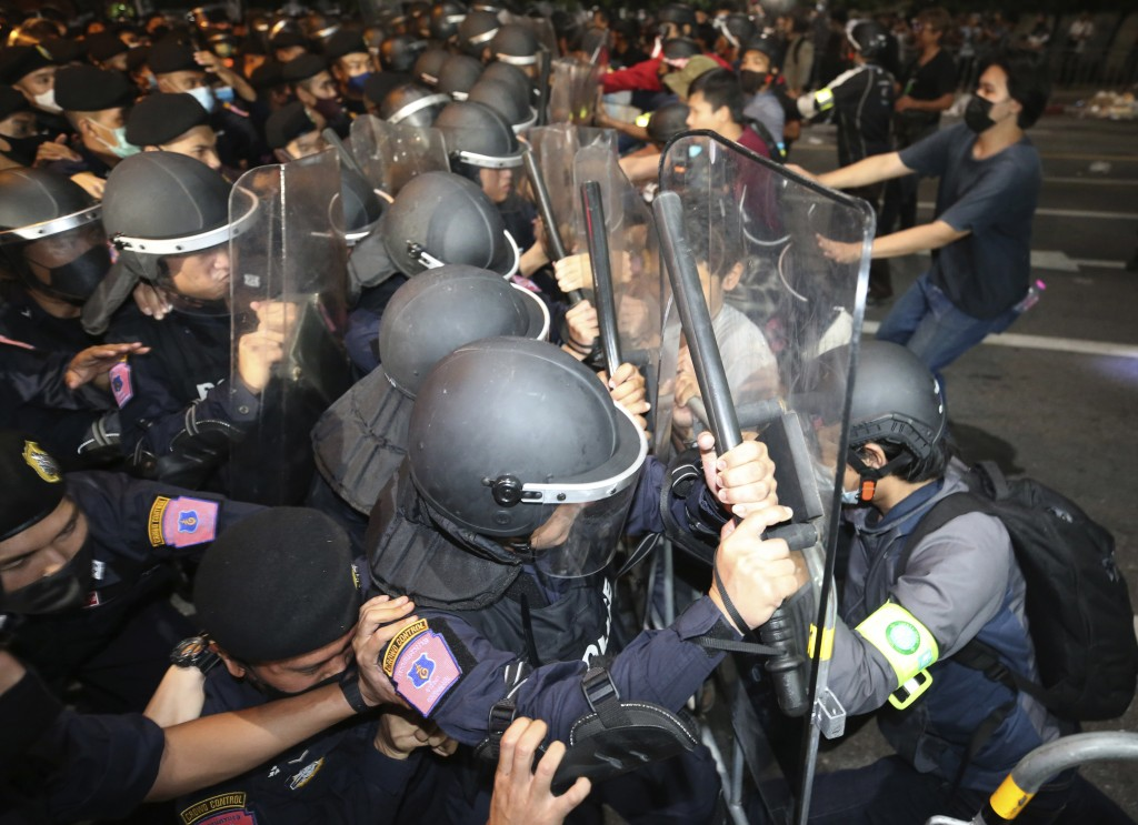 Pro-democracy protesters push Thai policemen with riot shields during a demonstration in Bangkok, Thailand, Thursday, Oct. 15, 2020. Thai police dispe...