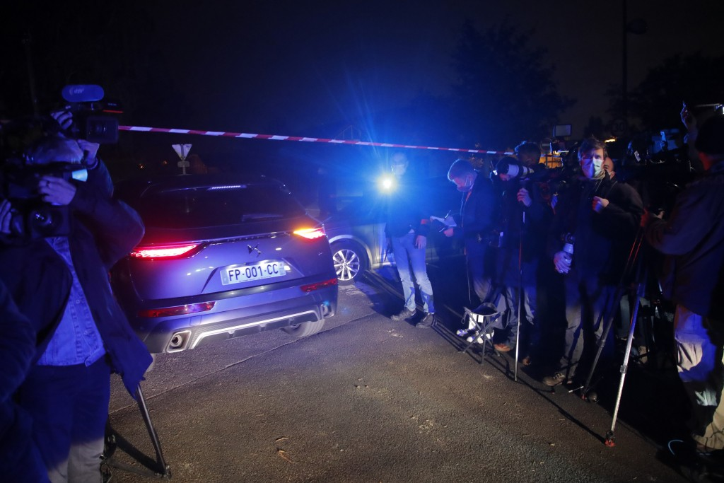 A police car enters the perimeter after a history teacher who opened a discussion with students on caricatures of Islam's Prophet Muhammad was decapit...