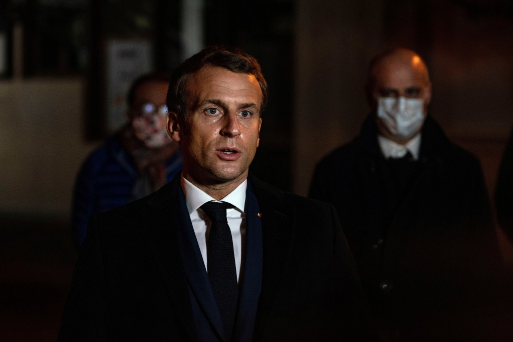 French President Emmanuel Macron speaks in front of a high school Friday Oct.16, 2020 in Conflans Sainte-Honorine, northwest of Paris, where a history...