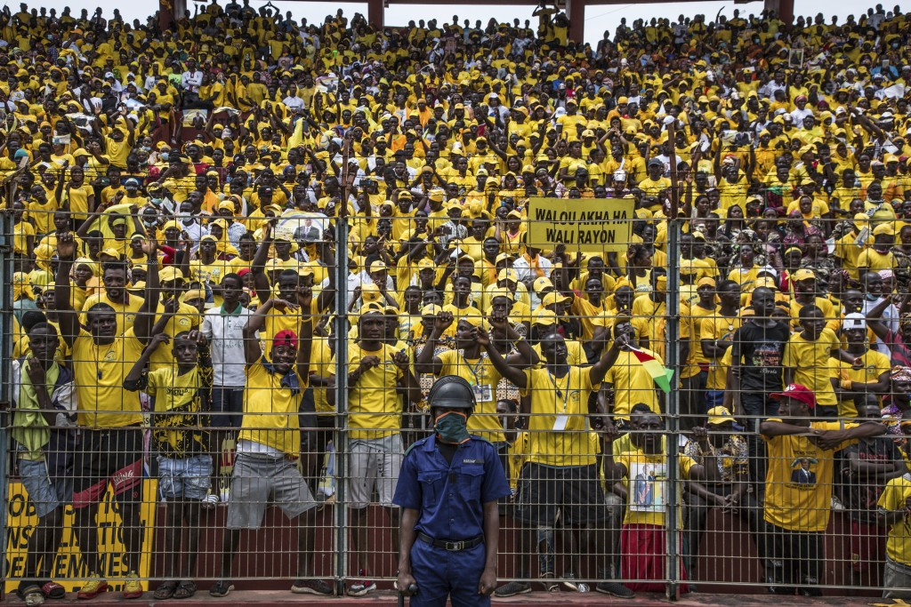 Supporters of Guinean's President Alpha Conde cheers his arrival at a campaign rally in Conakry, Guinea, Friday, Oct. 16, 2020. Conde is seeking a thi...