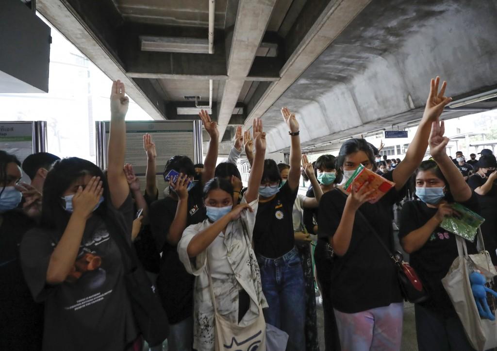 泰國反政府示威高舉象徵抗爭的三指手勢,在連續三日的抗議後,泰國警方16日晚間出動水車驅離示威者(照片來源:美聯社提供)