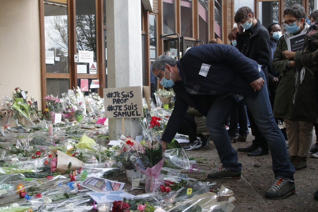 A man lays a flower outside the school where a slain history teacher was working, Saturday, Oct. 17, 2020 in Conflans-Sainte-Honorine, northwest of Pa...