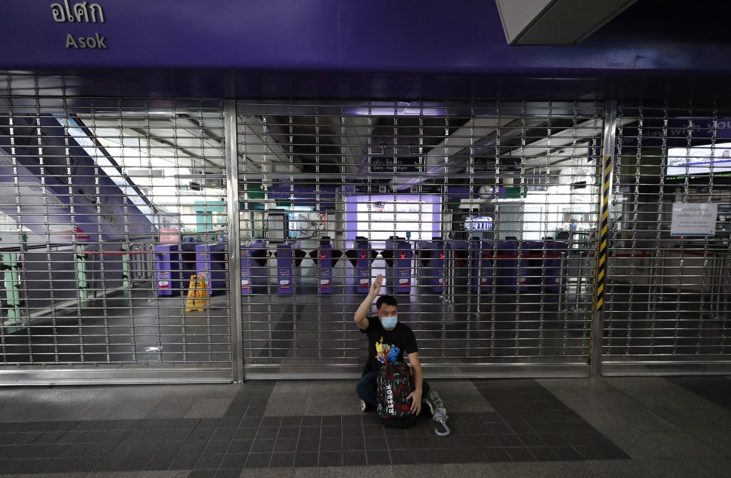A pro-democracy protesters raises three-finger salutes, a symbol of resistance, during a protest at a closed sky train platform in Bangkok, Thailand, ...