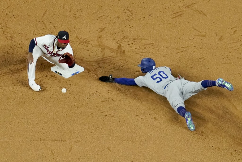 Los Angeles Dodgers' Mookie Betts steals seconds past Atlanta Braves second baseman Ozzie Albies during the sixth inning in Game 5 of a baseball Natio...