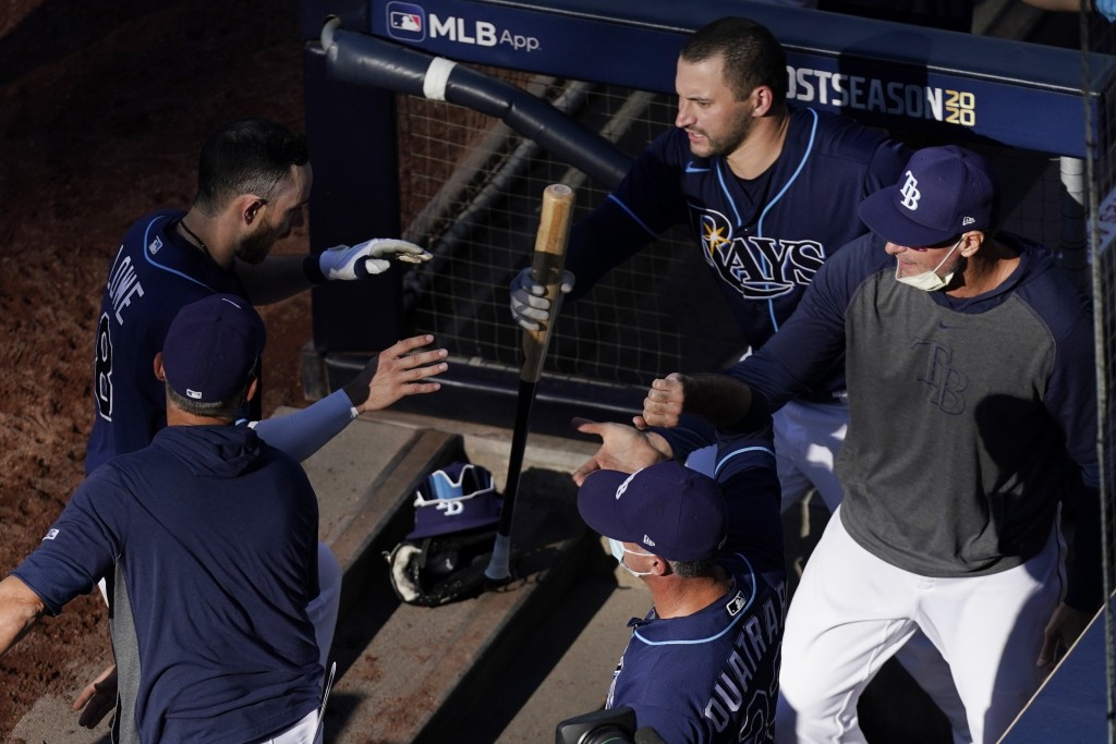 Tampa Bay Rays' Brandon Lowe, left, is congratulated after scoring on Willy Adames' RBI double during the second inning in Game 6 of a baseball Americ...