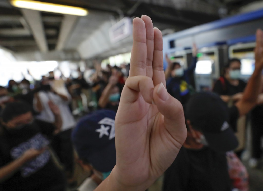 Pro-democracy protesters raise three-finger salutes, a symbol of resistance, during a protest at sky train platform in Bangkok, Thailand, Saturday, Oc...