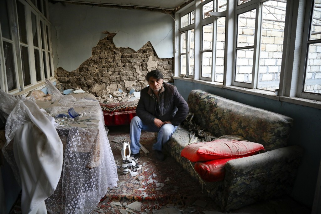A man sits in his destroyed house in a residential area that was hit by rocket fire overnight by Armenian forces, early Saturday, Oct. 17, 2020, in Gy...