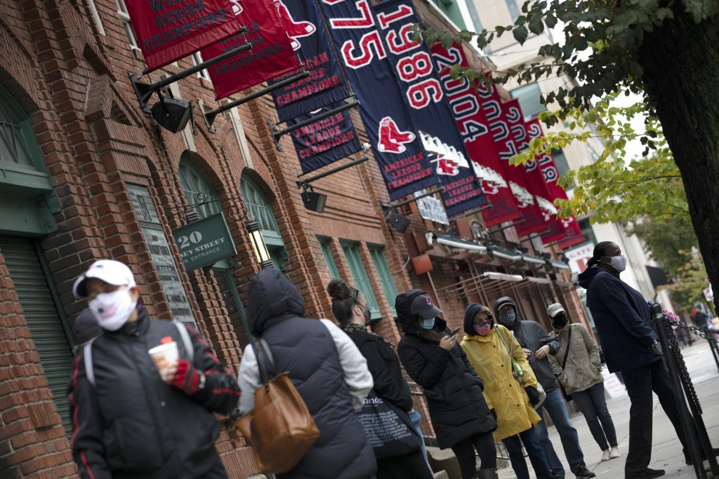 People wait in line for early voting to open at Fenway Park, Saturday, Oct. 17, 2020, in Boston. (AP Photo/Michael Dwyer)