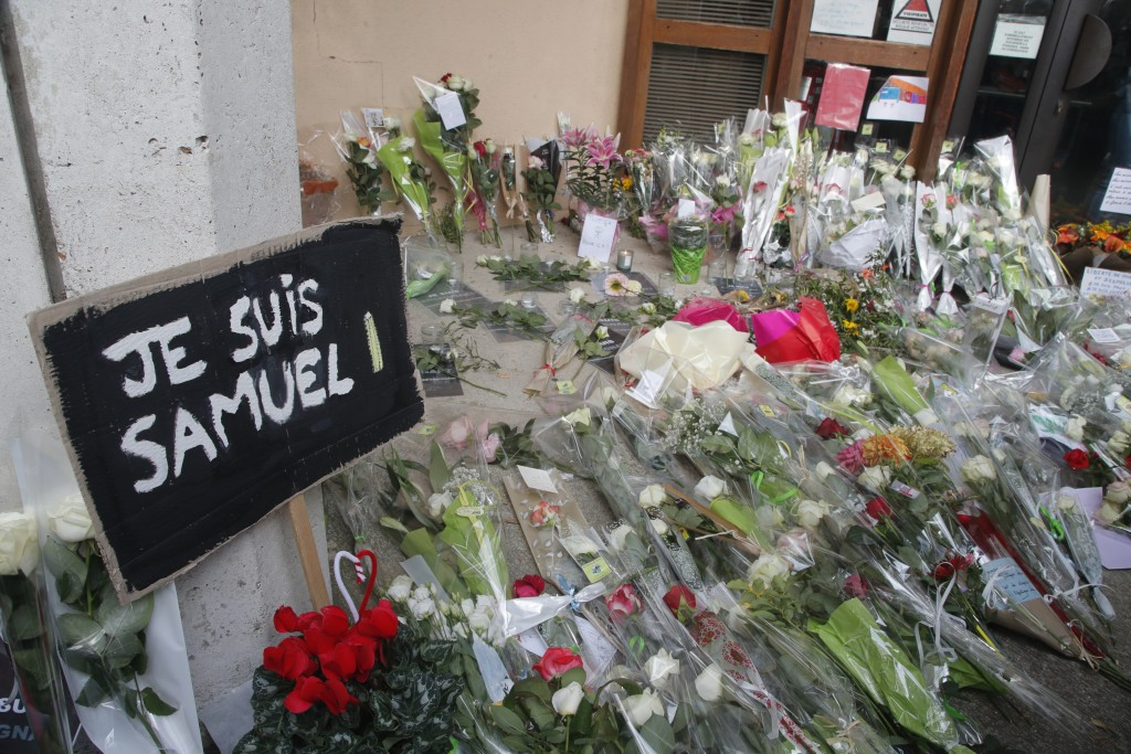 """A poster reading """"I am Samuel"""" and flowers lay outside the school where slain history teacher Samuel Paty was working, Saturday, Oct. 17, 2020 in Conf..."""