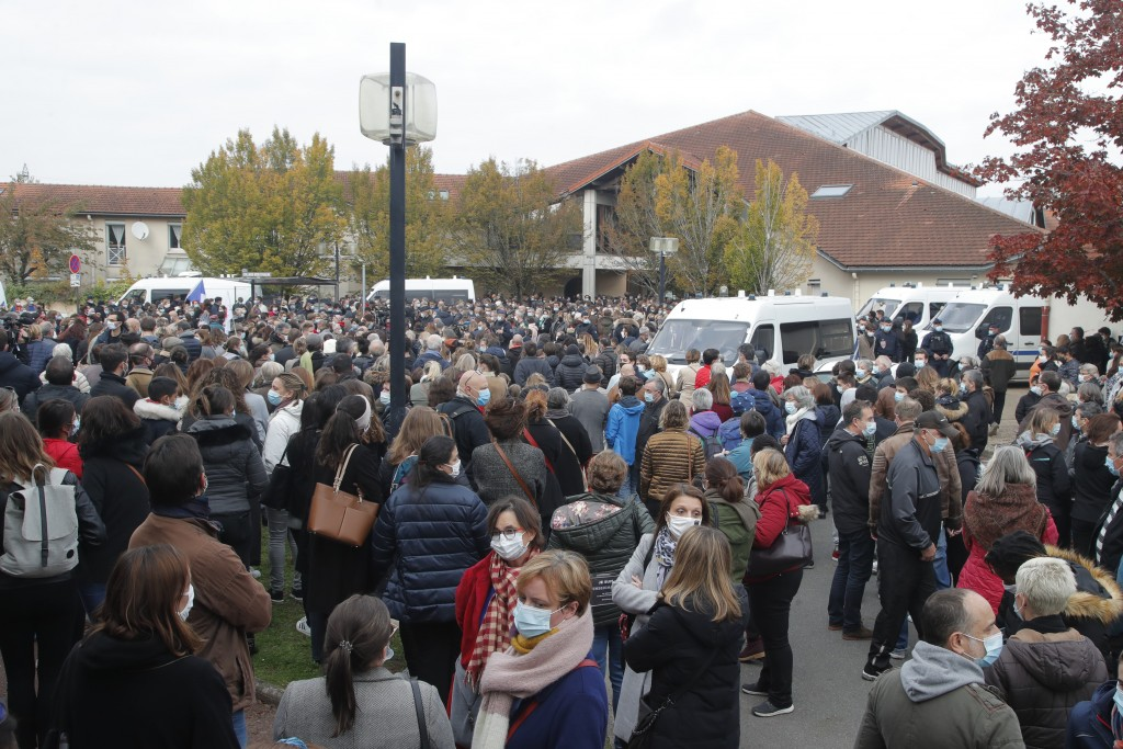 Residents gather outside the school where a slain history teacher was working, Saturday, Oct. 17, 2020 in Conflans-Sainte-Honorine, northwest of Paris...