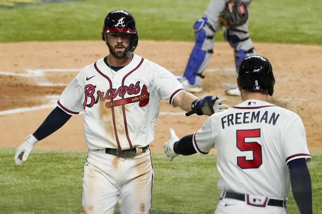 Atlanta Braves' Dansby Swanson celebrates with Freddie Freeman after scoring on a single by Cristian Pache during the second inning in Game 5 of a bas...